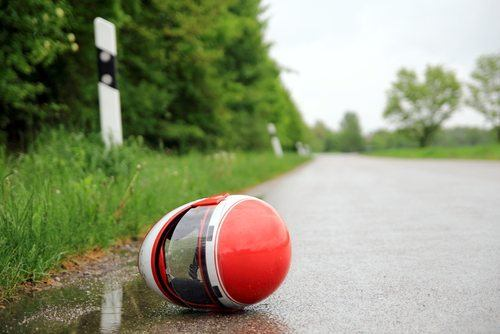 Red motorcycle helmet on a wet road