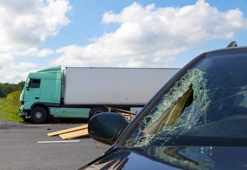 Car with broken window on a road with a large semi truck in the background following a collision