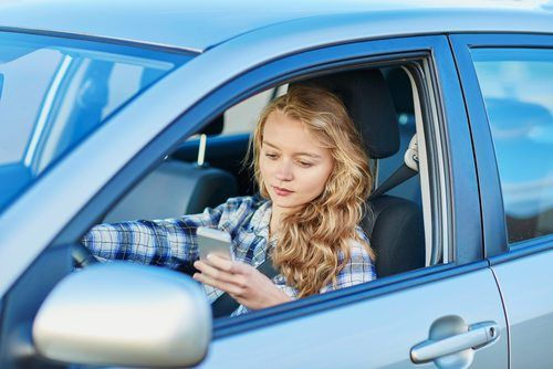Young woman using her smartphone while behind the wheel of her sedan